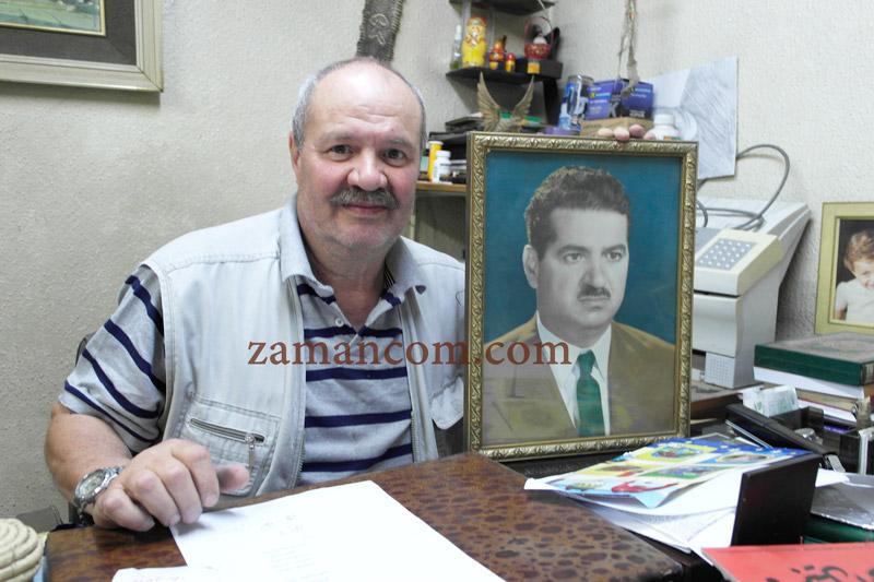 الابن نبيل يحتضن صورة والده مؤسس المكتبة
